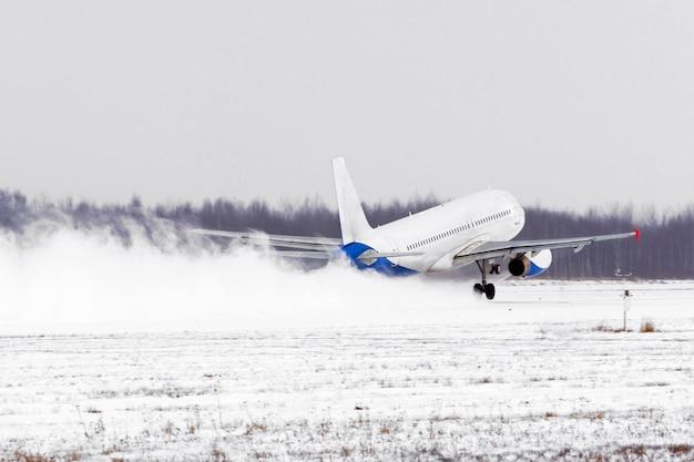 Samolot startuje z pokrytego śniegiem lotniska pasa startowego przy złej pogodzie podczas burzy śnieżnej