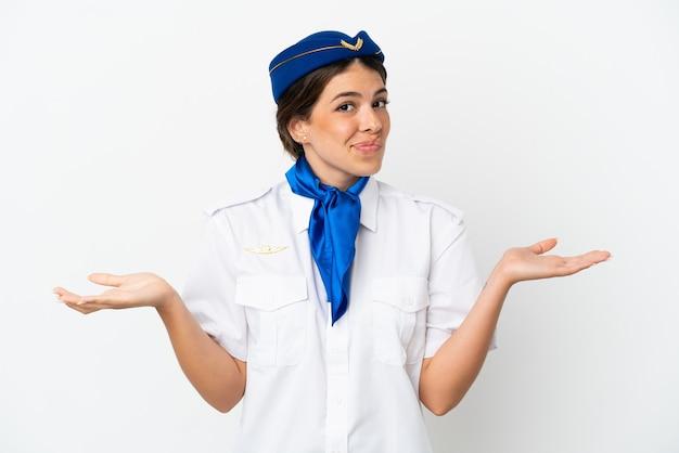 Samolot stewardessa kaukaska kobieta na białym tle mająca wątpliwości podczas podnoszenia rąk