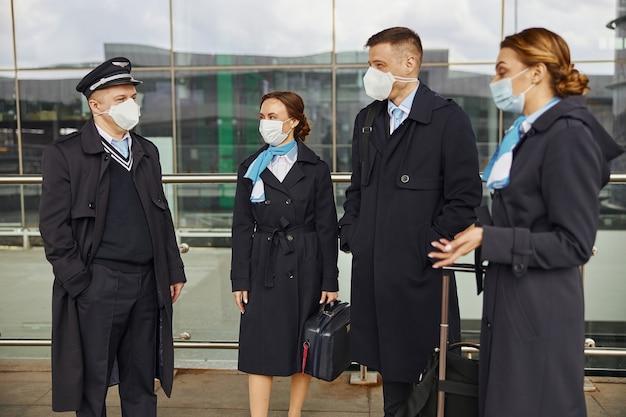 Samolot stojący i rozmawiający w pobliżu lotniska. kobiety i mężczyźni z bagażem noszą mundury i maski medyczne. pilot, stewardesa i stewardesy. praca w zespole. lotnictwo cywilne. koncepcja podróży lotniczych