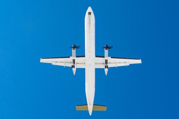 Samolot turbośmigłowy z silnikami śmigłowymi na skrzydłach przed lądowaniem na pasie startowym na lotnisku na tle błękitnego nieba.