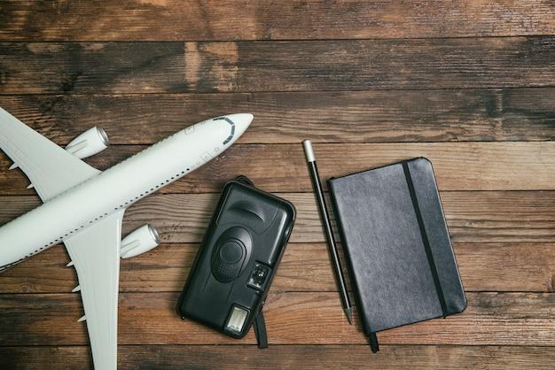 Samolot z notatnikiem i aparatem na drewnianym tle