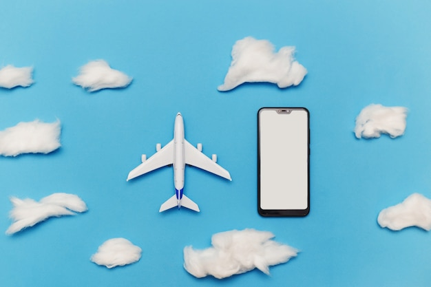 Samolot zabawka i smartfon z pustym ekranem na niebiesko