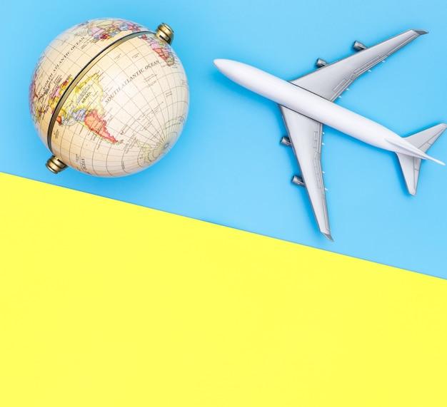 Samolot zabawka podróżuje po świecie kuli ziemskiej na niebiesko