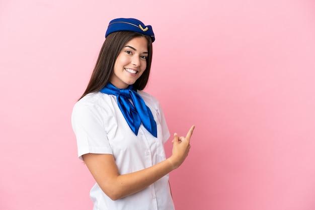Samolotowa stewardessa brazylijska kobieta odizolowana na różowym tle, wskazując do tyłu