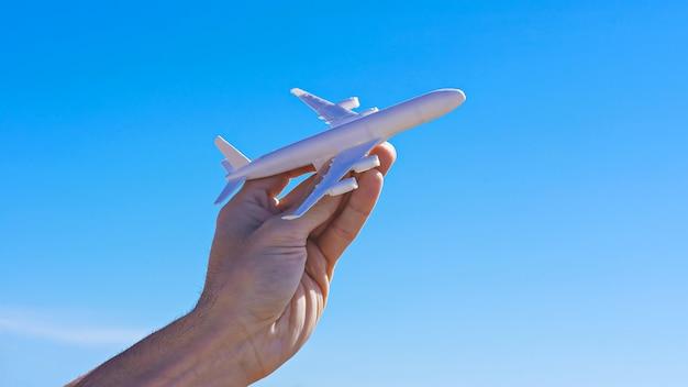 Samolotu model w ręce przeciw jasnemu niebieskiemu niebu