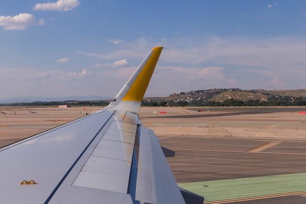 Samolotu skrzydło na pasie startowym przy lotniskiem na słonecznym dniu. koncepcja podróży i wakacji. widok z okna pasażera