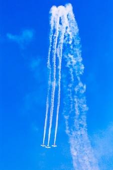 Samoloty na niebieskim niebie z białymi śladami