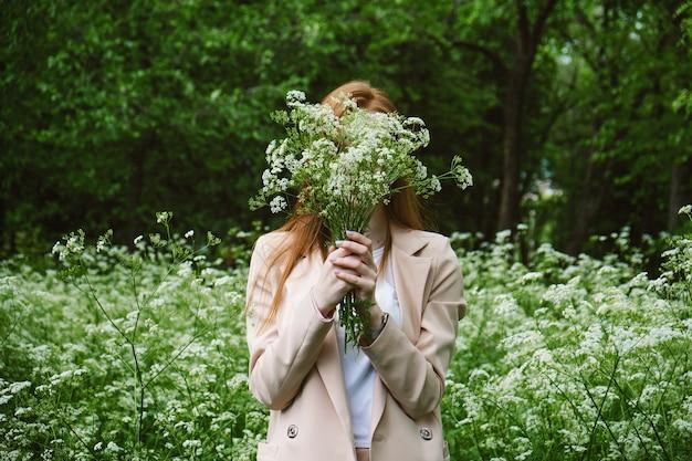 Samoopieka, dobre samopoczucie psychiczne, zdrowie psychiczne, uważność. młoda rudowłosa kobieta cieszy się życiem na łonie natury wśród kwiatów i zielonych drzew.