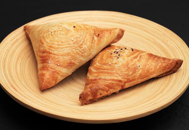 Samosa to pikantna mieszanka mięsa zawinięta w paczkę trójkątnego ciasta smażonego w głębokim tłuszczu na talerzu w ciemności.