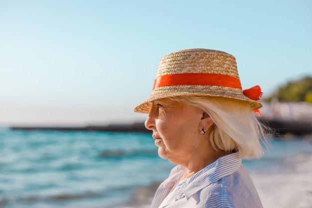 Samotna dorosła kobieta w słomkowym kapeluszu z czerwoną wstążką patrzy na widok na morze.