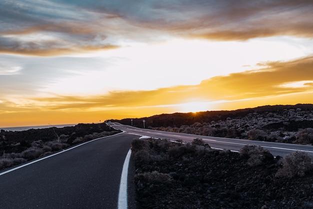 Samotna droga otoczona górami w pięknym zachodzie słońca