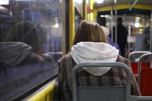 Samotna dziewczyna pasażerka w tramwajach komunikacji miejskiej wieczorem