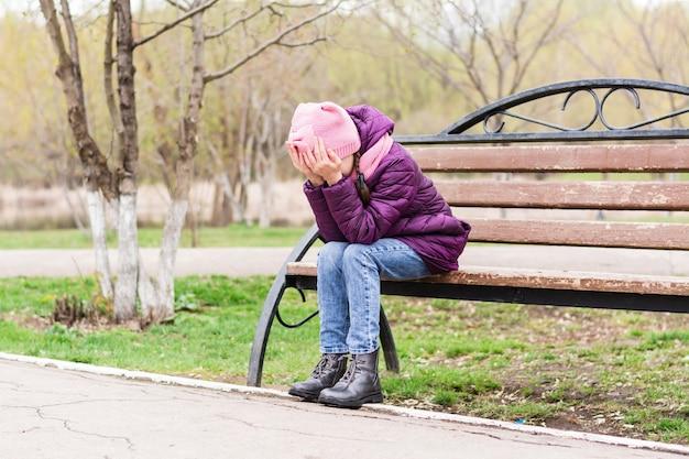 Samotna dziewczyna płacze zakrywając twarz dłońmi na ławce w parku. zdrowie psychiczne. młodzieńcze lata