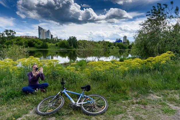 Samotna dziewczyna rozmawia online przez łącze wideo w pobliżu swojego roweru w parku miejskim. utrzymywanie dystansu podczas pandemii koronawirusa.