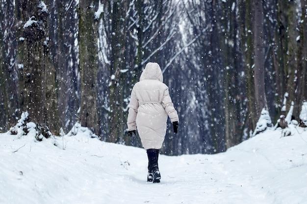Samotna dziewczyna spaceruje po parku zimą podczas opadów śniegu
