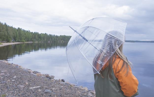 Samotna dziewczyna trzyma parasol blisko jeziora