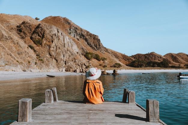 Samotna dziewczyna w letnim kapeluszu siedzi na skraju drewnianego molo i patrzy na jezioro