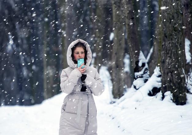 Samotna dziewczyna z telefonem w rękach w lesie podczas zamieci. spacer po zimowym lesie
