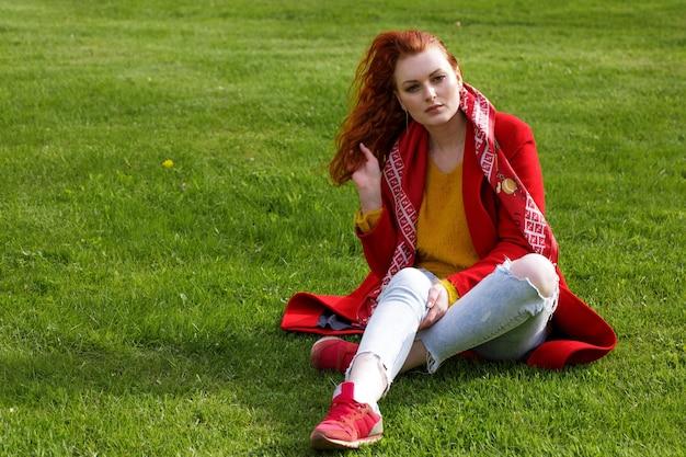 Samotna kaukaska rudowłosa kobieta w czerwonym płaszczu i jasnych dżinsach siedzi na zielonej trawie w parku w ciągu dnia