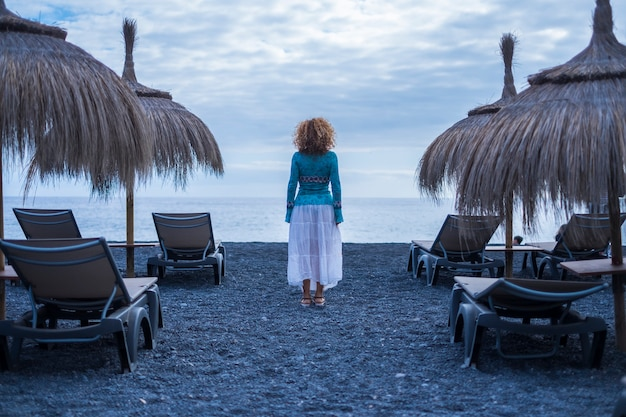 Samotna kobieta oglądana z tyłu stoi pośrodku pustych foteli i parasoli przeciwsłonecznych czekających i patrzących na spokojne fale oceanu. koncentracja i wolność alternatywna koncepcja stylu życia na zewnątrz