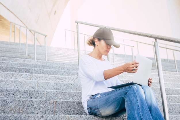 Samotna kobieta siedząca na schodach w czapce patrząca i pracująca z laptopem lub komputerem w spokoju w mieście - urbanistyczna koncepcja i biznesowa kobieta w ciszy