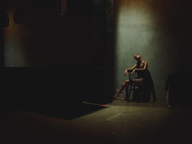 Samotna kobieta siedzi na krześle w ciemnym pokoju