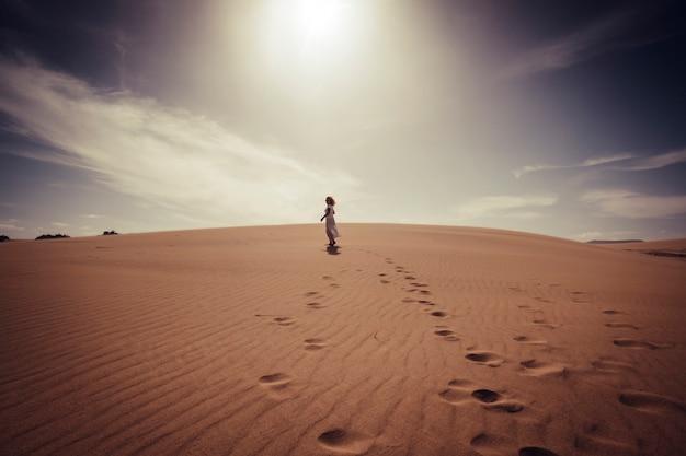Samotna kobieta spacerująca swobodnie po pustyni wydm w białej eleganckiej sukience, ciesząca się aktywnością na świeżym powietrzu i pięknym miejscem wokół - koncepcja podróży i stylu życia