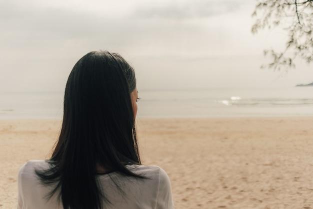 Samotna kobieta stoi na plaży i patrzy w morze.