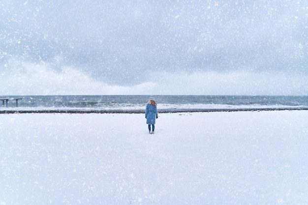 Samotna kobieta stoi w zamieci na brzegu śniegu