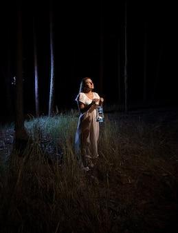 Samotna kobieta stojąca w przerażającym ciemnym lesie z lampą gazową