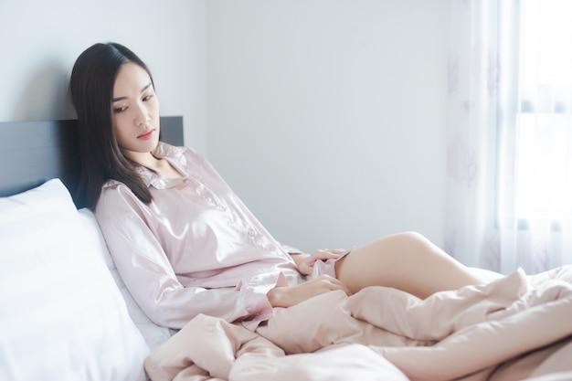 Samotna kobieta tęskni za kimś. smutna dziewczyna na łóżku