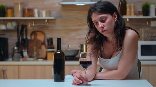 Samotna kobieta trzyma kieliszek czerwonego wina. nieszczęśliwa osoba cierpiąca na migrenę, depresję, choroby i stany lękowe, wycieńczona z objawami zawrotów głowy, mająca problemy z alkoholizmem.