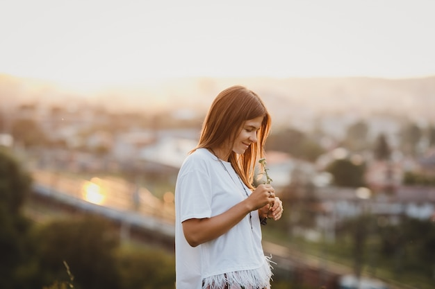 Samotna kobieta w białej koszuli stoi z kwiatem pola