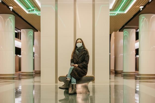 Samotna kobieta w medycznej masce na twarz, aby uniknąć rozprzestrzeniania się koronawirusa, siedzi ze smartfonem i czeka na pociąg metra. dziewczyna w masce chirurgicznej trzyma dystans społeczny w metrze.