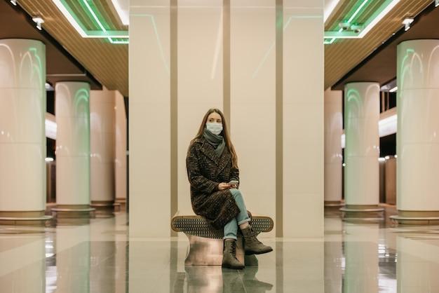 Samotna kobieta w medycznej masce na twarz, aby uniknąć rozprzestrzeniania się koronawirusa, siedzi ze smartfonem i czeka na pociąg metra. dziewczyna w masce chirurgicznej trzyma dystans w metrze.