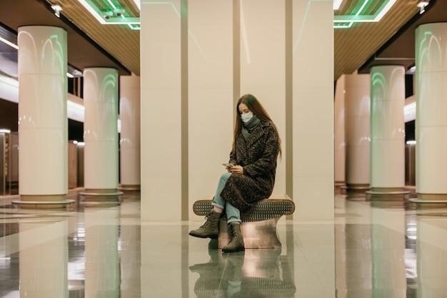 Samotna kobieta w medycznej masce na twarz, aby uniknąć rozprzestrzeniania się koronawirusa, siedzi ze smartfonem na peronie metra. dziewczyna w masce chirurgicznej trzyma dystans społeczny w metrze.