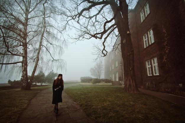 Samotna kobieta w mgłowym parku.