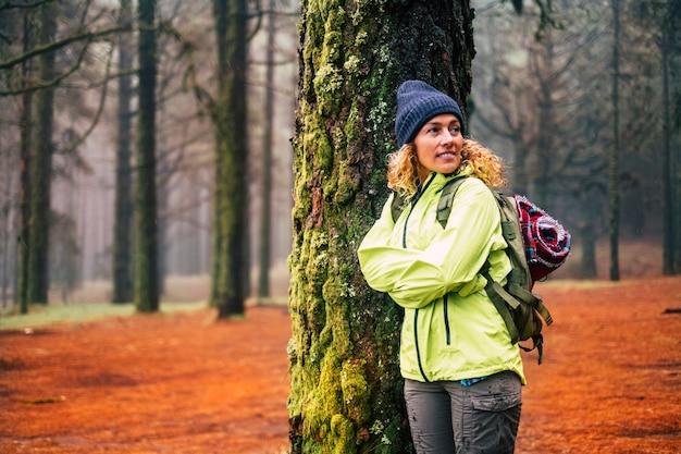 Samotna kobieta w zimnych i zimowych ubraniach cieszy się wypoczynkiem na świeżym powietrzu w lesie las z drzewami