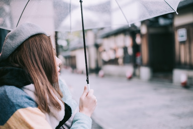 Samotna kobieta z parasolem czeka na deszcz na ulicy w japonii.