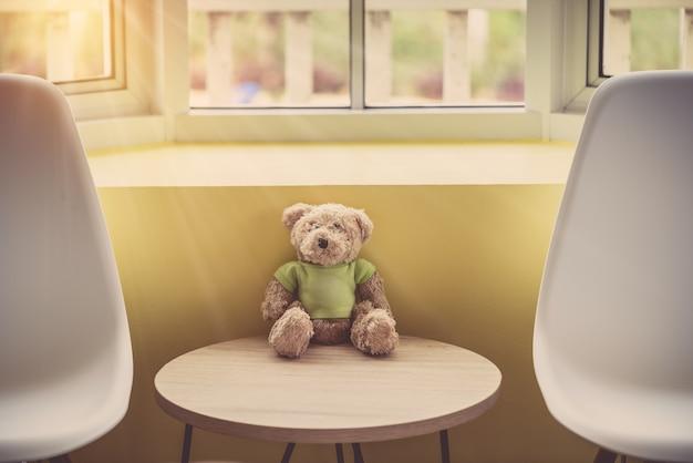 Samotna lalka niedźwiedzie w pobliżu okna