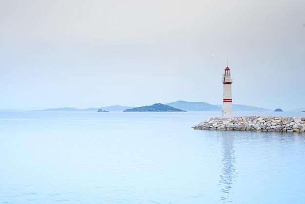 Samotna latarnia morska na kamiennej drodze pośrodku morza z widokiem na góry i mgłę