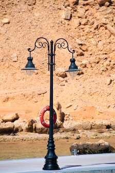 Samotna latarnia z kutego żelaza na nabrzeżu