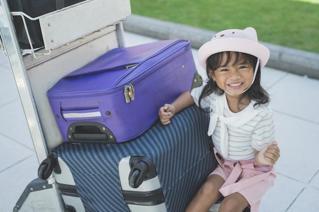 Samotna mała dziewczynka siedząca obok walizki na lotnisku