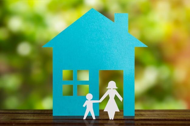 Samotna matka z synem w papierowym dowcipie niebieski dom. rozwiedziony.