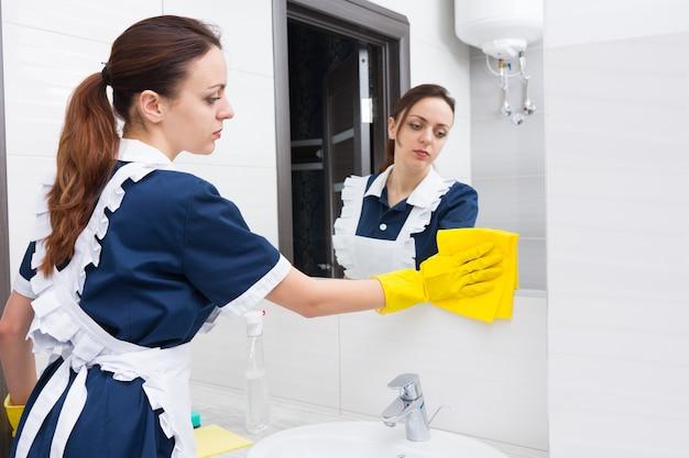 Samotna młoda dorosła pokojówka hotelowa za pomocą żółtej tkaniny i gumowych rękawiczek, aby uporządkować dolną część lustra w jasnej łazience