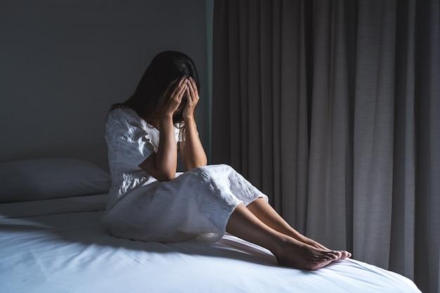 Samotna młoda kobieta czuje się przygnębiona i zestresowana siedząc w ciemnej sypialni