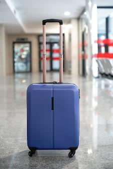 Samotna niebieska walizka na środku stacji