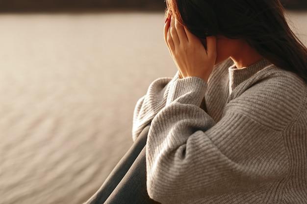 Samotna nieszczęśliwa kobieta siedzi w pobliżu rzeki