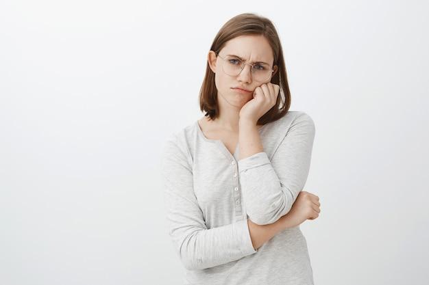 Samotna niezadowolona i nieszczęśliwa śliczna młoda kobieta w okularach z krótkimi brązowymi włosami marszczy brwi i dąsa się ze smutku opierając twarz na dłoni wpatrując się z obojętnością w szarą ścianę