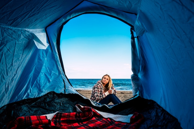 Samotna piękna blondynka z namiotu na plaży dla alternatywnej wolności biwakowanie na świeżym powietrzu. wakacje na plaży w pobliżu fal oceanu na kalifornijski styl życia surferki blondynki